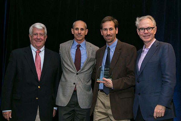 Dr. Welford receiving his award. With him are, left to right, Barry L. Hoeven, founder of Kure It Cancer Research; Todd Perry, board member, Kure It Cancer Research; and Charles L. Sawyers, MD, immediate past president of the AACR.